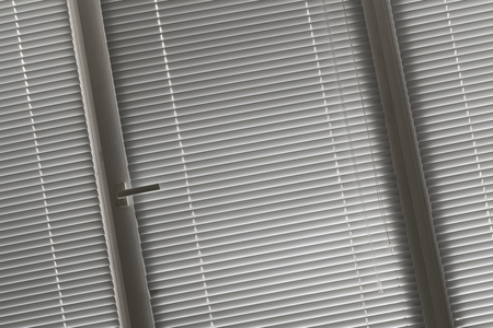 window shade: slanted view on grey horizontal jalousie in the office window
