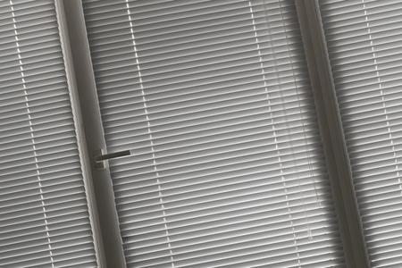 jalousie: slanted view on grey horizontal jalousie in the office window