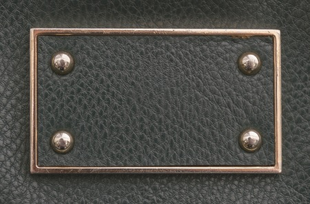 imitation leather: texture sample of the black imitation leather tag with metal border and rivets Stock Photo