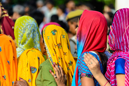 MATHURA, INDIA - AUGUST 17, 2014: women in colorful saris waiting in a queue at Krishna Birthday Festival Editorial