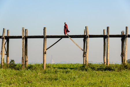 AMARAPURA, MYANMAR - FEBRUARY 20, 2014: monk walking over U Bein Bridge, the worlds longest teakwood bridge Editorial
