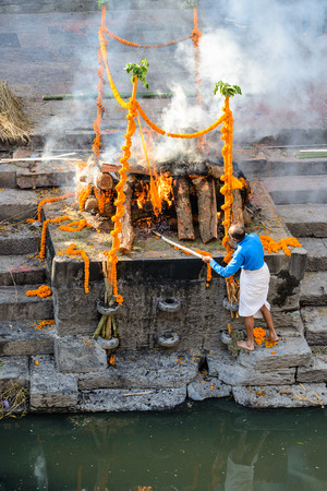 PASHUPATINATH, NEPAL - MARCH 26, 2014: barefooted man controls fire on cremation ghats in Pashupatinath, Kathmandu valley Editorial