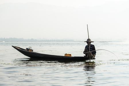 INLE LAKE, MYANMAR - FEBRUARY 15, 2014: burmese woman working on a weaving loom: Burmese fisherman on bamboo boat catching fish in traditional way