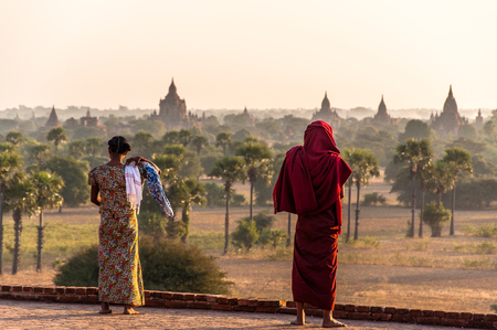 A burmese woman with a monk looking over the pagdodas of Bagan, Pyathada Temple in Bagan, Myanmar