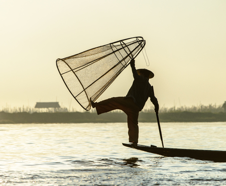 Burmese fisherman on bamboo boat catching fish in traditional way with handmade net. Inle lake, Myanmar (Burma)