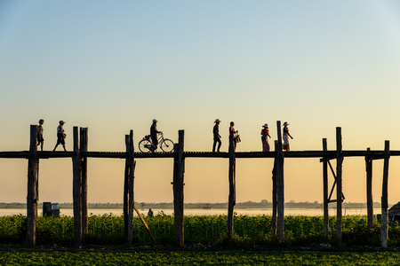 AMARAPURA, MYANMAR - FEBRUARY 20, 2014: Silhouetted people on walking on the U-Bein Bridge at sunset, U Bein Bridge, the worlds longest teakwood bridge Editorial