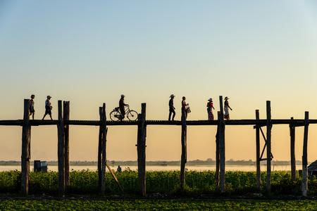 U Bein 橋上夕暮れ、U Bein の橋、世界の最も長い橋を歩いてアマラプラ、ミャンマー - 2014 年 2 月 20 日: シルエット人 報道画像