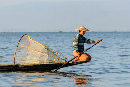 INLE LAKE, MYANMAR - FEBRUARY 16, 2014: Burmese fisherman on bamboo boat catching fish in traditional way with handmade net. Inle lake, Myanmar (Burma)