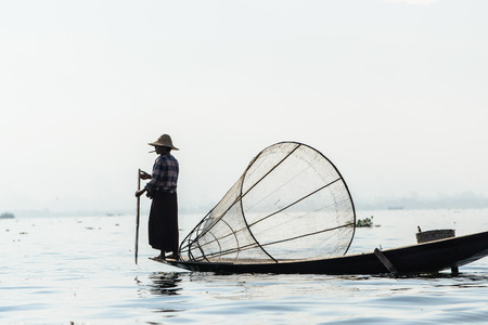 INLE LAKE, MYANMAR - FEBRUARY 15, 2014: Burmese fisherman on bamboo boat catching fish in traditional way with handmade net. Editorial