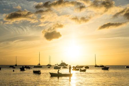 silhouetted fishermen at sunset, Bay Lanse ? la barque Guadeloupe Stock Photo