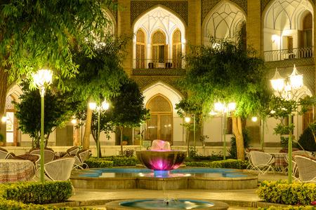 イスファハン、イラン - 2015 年 4 月 25 日: 照らされた庭のホテル Abbasi、古代隊商宿 報道画像