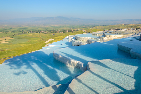 The enchanting pools of Pamukkale in Turkey. Pamukkale contains hot springs and travertines, terraces of carbonate minerals left by the flowing water. Stock Photo