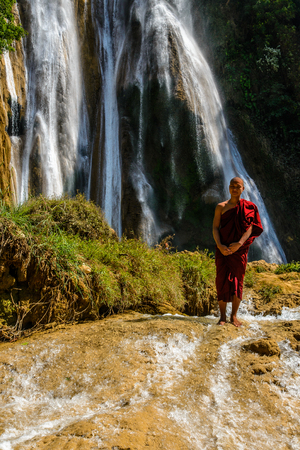 ANISAKAN, MYANMAR - FEB 22, 2014: Buddhist monk in front of Anisakan Waterfall Editorial