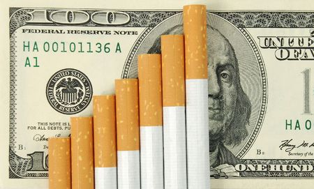 bad habit: the cigarettes laying on american money.  Cost of a bad habit.