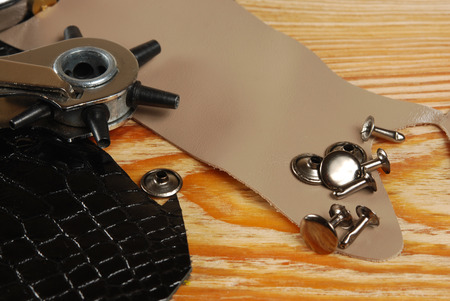 rivets: Workplace tailor with pieces of leather, tool for punching holes and rivets Stock Photo