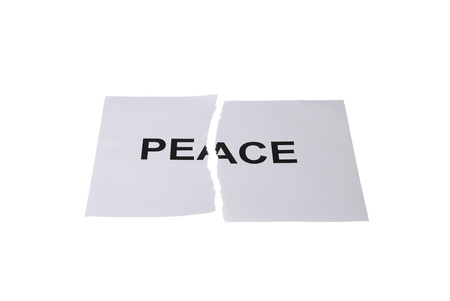 broken contract: The word peace written on paper and torn into two parts