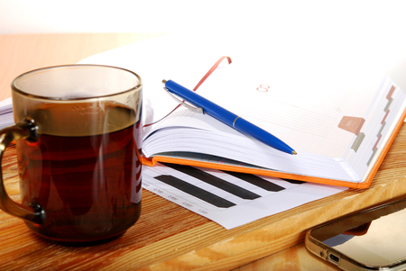 non alcoholic: The cup of tea on a wooden table with a notebook and pen