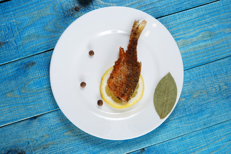 fish vendor: Grilled fish with lemon, round pepper and bay leaf on a plate on the blue wooden background