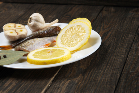 fish vendor: Raw fish with lemon, garlic, round pepper and bay leaf on a white plate on a wooden background Stock Photo