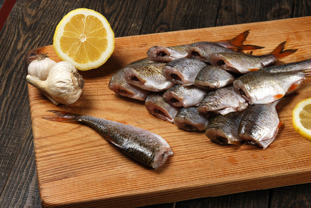 Raw fish with lemon, garlic, round pepper and bay leaf on a chopping board