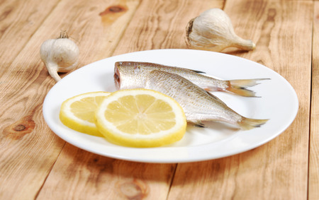 fish vendor: Raw fish with lemon and garlic on a white plate on a wooden background Stock Photo