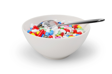 Medicine pills and capsules in a breakfast bowl with a spoon