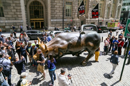 charging bull: Tourists posing with Charging Bull in New York Editorial