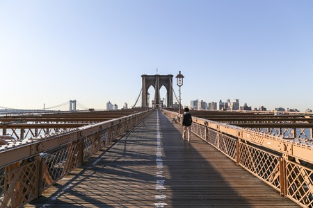pedestrian bridges: Young man walks across the Brooklyn Bridge