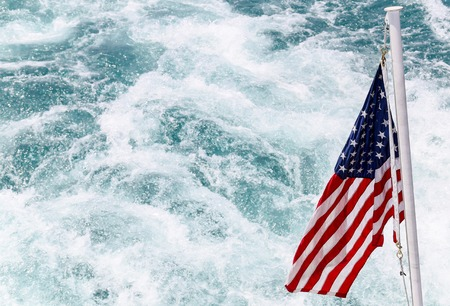 The American flag waving over the wake of a ship