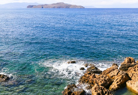 islets: The uninhabited islets of Agioi Theodoroi off the coats of western Crete. In the foreground some rocks with sea spray.