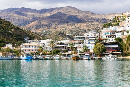 The village of Agia Galini, Crete, Greece with colorful houses, hotels and taverns rising on a slope. In the foreground  the harbor basin with several boats, in the back mountains.
