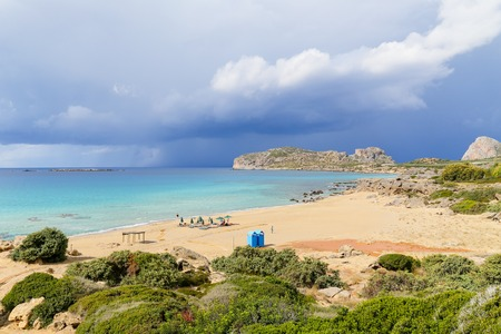 Falassarna beach in Crete with only a few people. In the sky there are dark clouds.