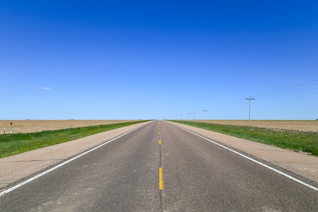 great plains: Highway between fields near Lakin in Kansas, USA, with transmission linves to one side of it.