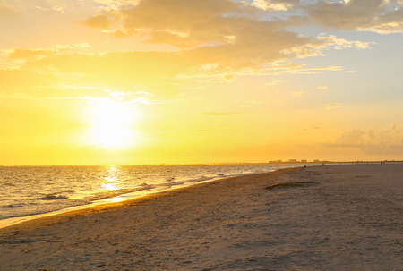 myers: The sun setting in Fort Myers Beach with the skyline and Matanzas Pass Bridge in the distance and the beach in the foreground. Stock Photo