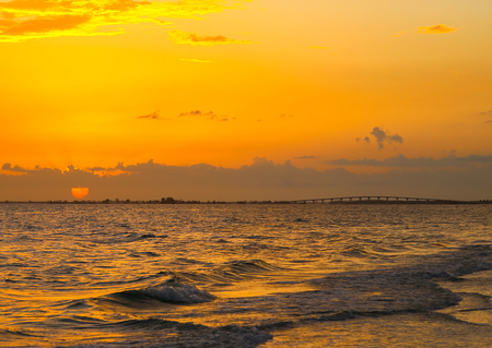 myers: The sun sinking into the Gulf of Mexico in Fort Myers Beach with gentle waves and the Matanzas Pass Bridge in the back.
