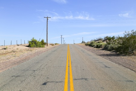 sonoran desert: Lonely road in the Sonoran Desert, Arizona, USA, with some shrubs growing on arid ground and overhead power cables to one side. Stock Photo
