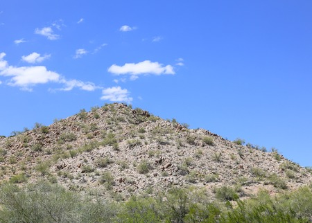 Rugged hill in the Sonoran Desert, Arizona, USA, with some shrubs growing on and around it. The sky is blue.