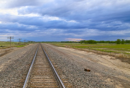 enclosure: Railroad tracks with transmission lines to the one side and an enclosure to the other near Las Animas in Colorado, USA. Stock Photo