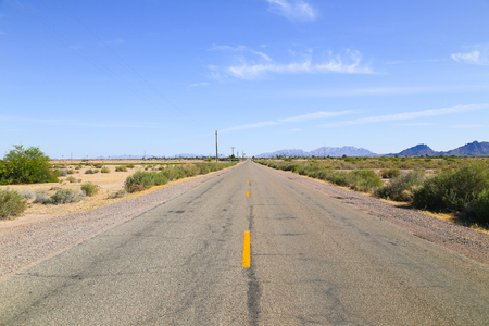 Road through the Sonoran Desert, Arizona, USA, with overhead power cables to one side of the road, in the back a settlement and a mountain range. Stock Photo