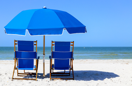 A pair of blue beach chairs and a blue sunshade on the beach in Fort Myers Beach viewing the Gulf of Mexico. Stock Photo