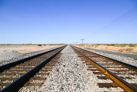 Railroad tracks in the Sonoran Desert, Arizona, USA, with overhead power cables to one side and the Old US Highway 80 to the other and a mountain range in the back.