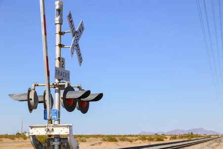 Railroad crossing in the Sonoran Desert, Arizona, USA, secured by railroad gates and lights. Stock Photo