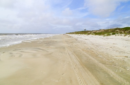 the surge: Looking down the beach on Jekyll Island with the surge of waves to the left and the sand dunes to the right.