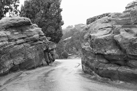Winding road through red rocks in Garden of the Gods public park in Colorado Springs in Colorado, USA. The image is monochrome.