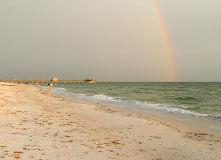 포트 마이어스 비치, 미국 - 해변을 따라 산책하는 파도의 파동. 뒤쪽에는 무지개와 포트 마이어스 비치 부두가 있습니다.