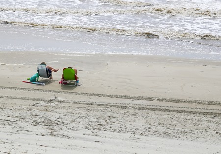 the surge: Two people sitting in beach chairs on the beach next to the surge of waves in Jekyll Island.