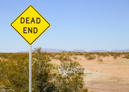 Dead End sign in the Sonoran desert, Arizona, USA, with a mountain range in the back and shrubs growing on arid ground.