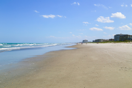 cape canaveral: Looking down the beach in Cocoa Beach with only few people walking and sunbathing and the surge of the Atlantic Ocean to the left. Stock Photo