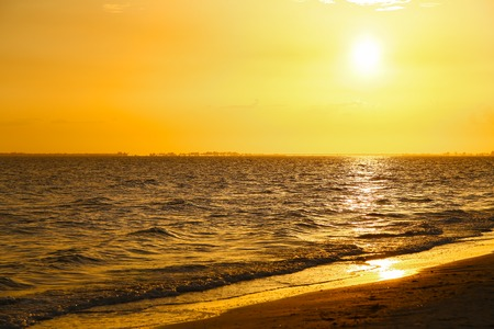 myers: The sun setting on a bright orange sky above the Gulf of Mexico in Fort Myers Beach with the beach in the foreground.