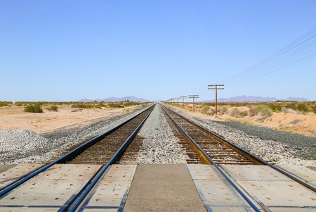 Railroad tracks at a crossing in the Sonoran Desert, Arizona, USA, with overhead power cables to one side and the Old US Highway 80 to the other and a mountain range in the back.